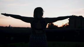 女孩站立与她的胳膊被伸出反对惊人的日落 令人惊讶的心情!好的射击 影视素材