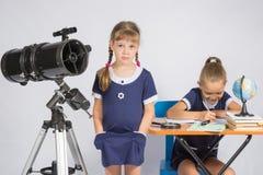 女孩站立在一台望远镜用他的在他的口袋的手,获得另一个的女孩坐在桌上的乐趣并且写道 免版税图库摄影