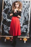 女孩站立在一条女衬衫和红色裙子的黑墙壁前面的巫婆为与蜡烛的万圣夜 免版税图库摄影