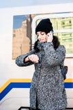 女孩站立在火车旁边,看她的手表和谈话在电话-接近  免版税库存照片
