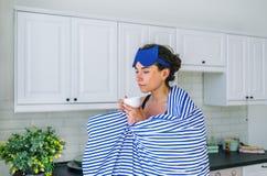 女孩站立在现代厨房,妇女的饮料茶结束了眼睛梦想 免版税库存图片