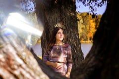 女孩站立在秋天叶子的一棵树 免版税库存照片