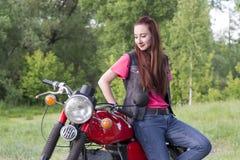 女孩站立近的葡萄酒摩托车户外 免版税图库摄影