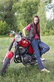 女孩站立近的葡萄酒摩托车户外 库存照片