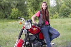 女孩站立近的葡萄酒摩托车户外 免版税库存照片