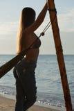 女孩站立靠近吊床和神色在海,休息,放松 黎明 牛仔裤的女孩有长的头发的 免版税库存照片