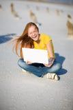 女孩笑的笔记本 免版税库存照片