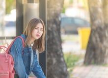 女孩等待公共汽车 乏味青少年等待做父母室外在金属长凳开会 图库摄影