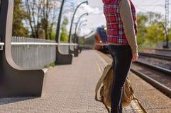 女孩等待的火车的腿有backback的 免版税库存图片
