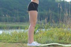 女孩简而言之和运动鞋的照片苗条腿在近森林 免版税库存照片