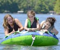 女孩管材在湖 免版税库存图片