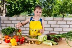 女孩繁忙的装瓶的新鲜蔬菜 免版税库存照片