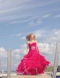 女孩红色正式舞会礼服旋转的小船船坞 免版税图库摄影