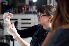 女孩纹身花刺大师在工作 免版税图库摄影