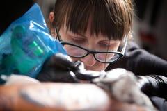女孩纹身花刺大师在工作 图库摄影