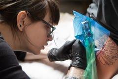 女孩纹身花刺大师在工作 免版税库存照片