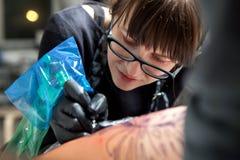 女孩纹身花刺大师在工作 库存图片