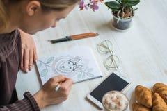 女孩绘与铅笔多壳在一个咖啡馆的白色板料在白色木桌光背景 免版税库存照片
