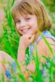 女孩绿色愉快的草甸微笑的少年 免版税库存图片