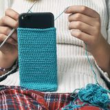 女孩编织羊毛智能手机盒 库存照片