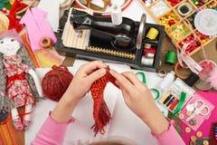 女孩编织玩偶衣裳,顶视图,缝合的辅助部件顶视图,裁缝工作场所,许多为针线,手工制造和手反对 库存照片