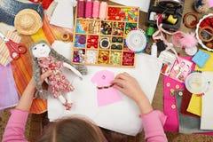 女孩缝合玩偶衣裳,顶视图,缝合辅助部件顶视图,裁缝工作场所,许多为针线,手工制造和手反对 库存照片