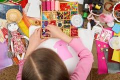 女孩缝合玩偶衣裳,顶视图,缝合辅助部件顶视图,裁缝工作场所,许多为针线,手工制造和手反对 免版税库存图片