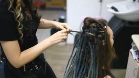 女孩美发师编织沙龙的dreadlocks客户 股票视频