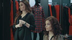 女孩美发师谈话在妇女` s衣物精品店的晚上构成  股票录像