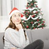 女孩考虑圣诞节 免版税图库摄影