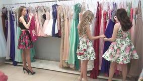 女孩考虑在一个精品店的礼服与高价衣服 股票录像