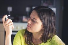 女孩考虑鼻子的一朵浪花 寒冷的治疗,流感 库存图片