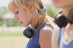 女孩耳机低劣的无线年轻人 库存图片