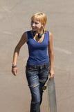女孩耳机低劣的溜冰者年轻人 免版税库存照片