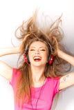 女孩耳机听的音乐微笑 图库摄影