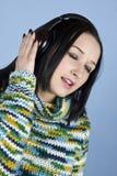 女孩耳机听音乐唱歌 免版税图库摄影