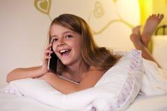 女孩聊天在有她的朋友的电话的,浅深度 免版税库存照片
