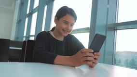 女孩聊天生活方式的少年在一个智能手机的信使沟通在咖啡馆在桌阳光 影视素材