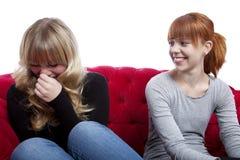 女孩联系和坐长沙发 免版税库存图片