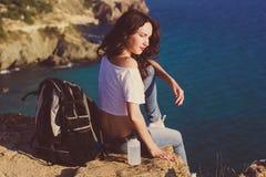 女孩背包徒步旅行者坐在海视图的岩石 免版税库存图片