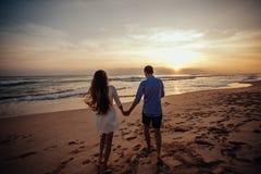 女孩背面图和男孩互相拥抱 走在海滩的年轻夫妇剪影在令人惊讶的日落藏品 库存图片