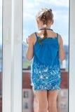 女孩背面图站立在玻璃窗后的蓝色礼服的 免版税图库摄影