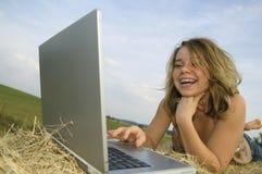 女孩膝上型计算机俏丽的工作 免版税库存图片