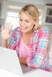 女孩膝上型计算机坐了少年使用 免版税库存图片