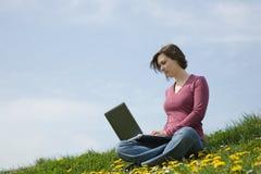 女孩膝上型计算机工作 免版税图库摄影