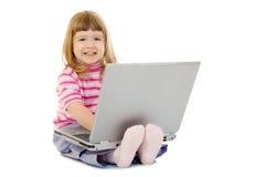 女孩膝上型计算机微笑的一点 库存图片