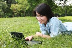女孩膝上型计算机户外微笑的年轻人 免版税库存照片