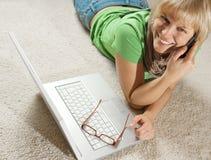 女孩膝上型计算机电话 免版税库存照片