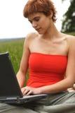 女孩膝上型计算机运作的年轻人 免版税库存图片