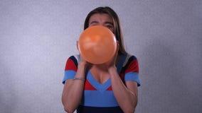 女孩膨胀橙色气球,球吹去,女孩笑 r 股票视频